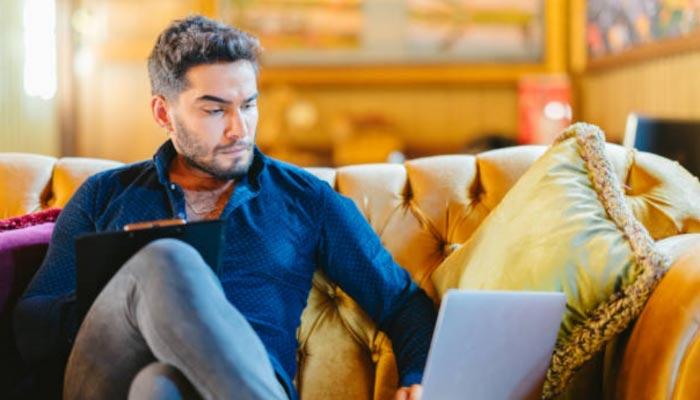 home de meia idade fazendo checkin no sofá de casa através de um notebook com Wi-fi