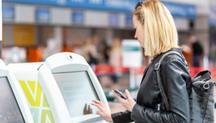 mulher fazendo check-in no tottem do aeroporto