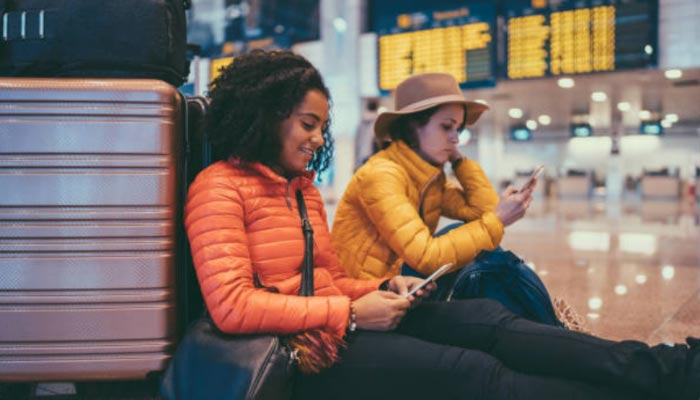 duas mulheres sentadas no chão do aeroporto fazendo check-in online