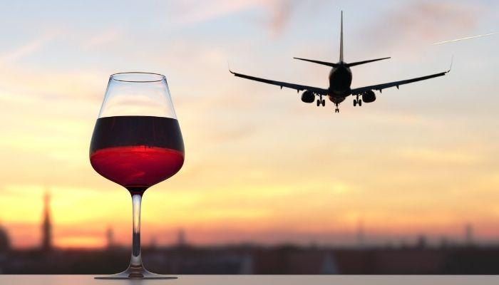 garraf de vinho sobre balcão vendo avião decolar