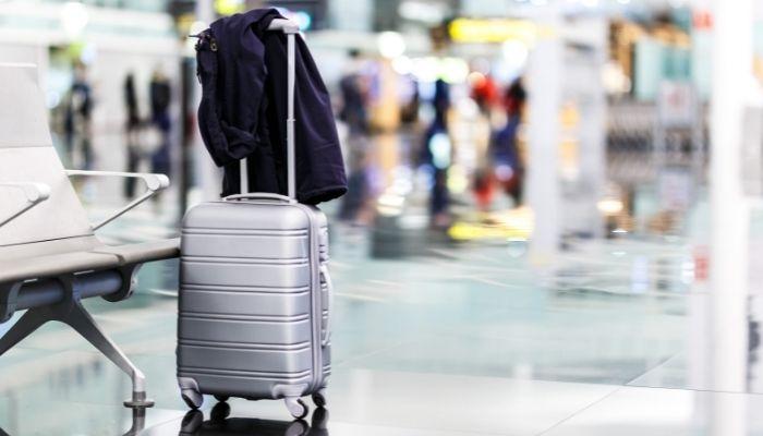 mala de vinhos no aeroporto na área de embarque com casaco por cima
