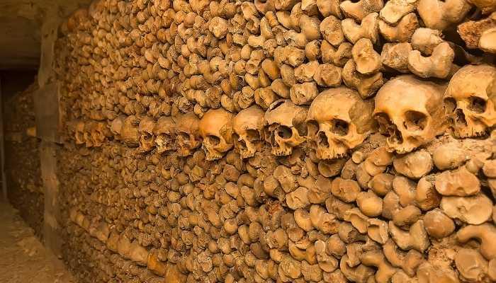 Crânios antigos sobrepostos formam a parede dAs Catacumbas da Via Ápia Antiga